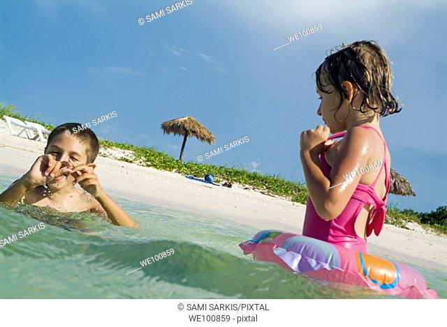 Boy and girl swimming in the tropical water at Cayo Jutias, Cuba