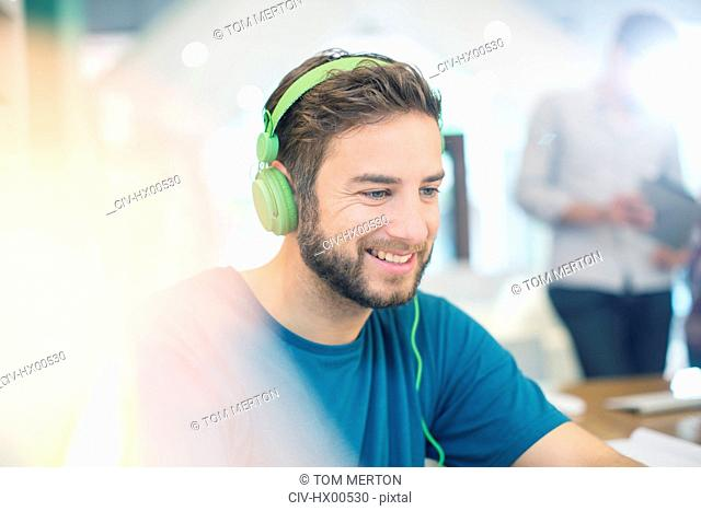 Smiling creative businessman listening to headphones in office