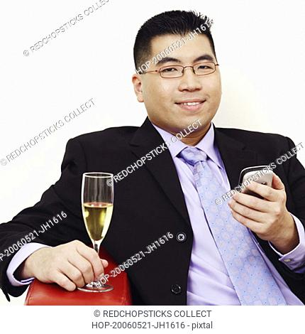 Portrait of a businessman holding a champagne flute and a mobile phone