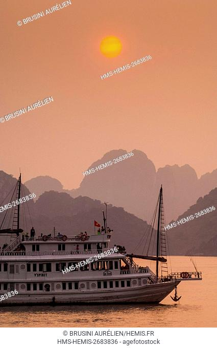 Vietnam, Gulf of Tonkin, Quang Ninh province, Ha Long Bay (Vinh Ha Long) listed as World Heritage by UNESCO (1994), sunset on a tourist sampan amid the iconic...