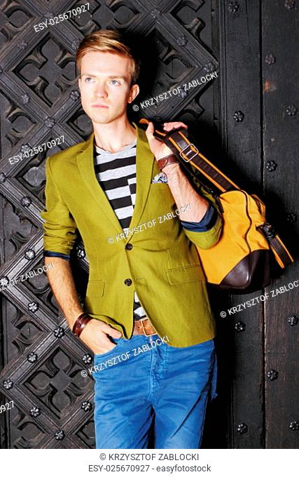 young handsome man fashion model casual style with bag on street of old town gdansk poland europe