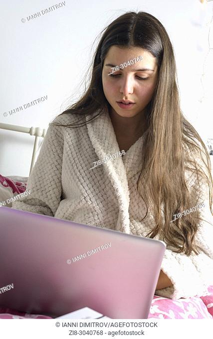 Teenage Schoolgirl, 16 years old studies in bed, Surrey, UK