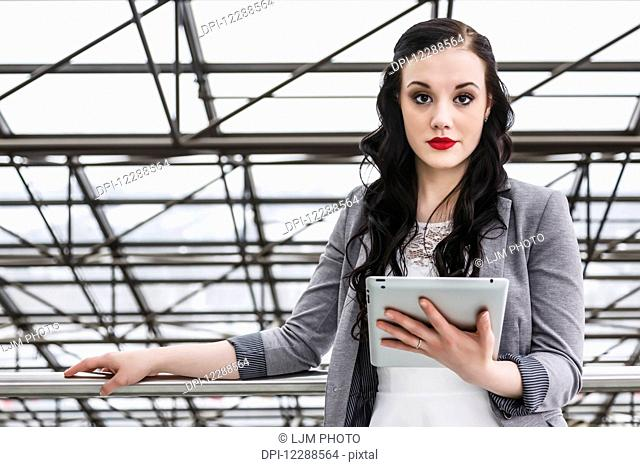 Attractive young millennial business woman with tablet in downtown office building; Edmonton, Alberta, Canada