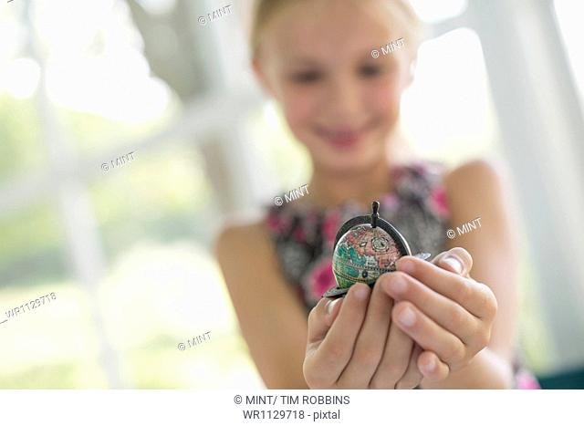 A young girl holding out a small globe in the palms of her cupped hands