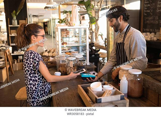 Customer making a mobile payment at counter