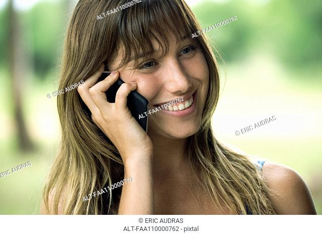 Young woman talking on cell phone and smiling