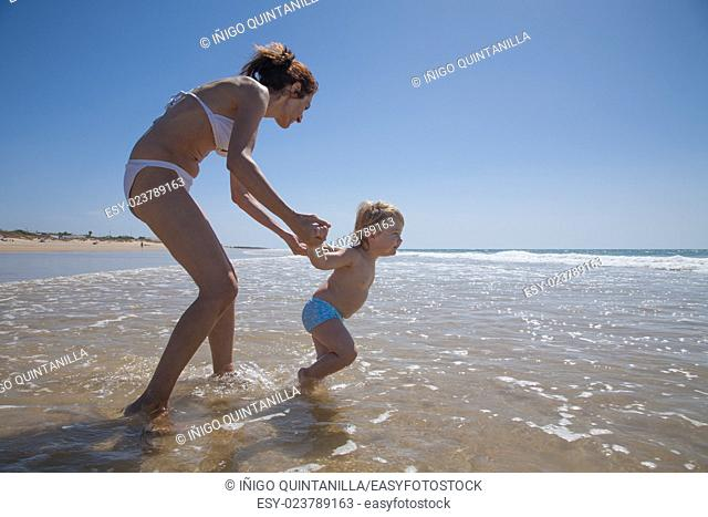 summer family of two years blonde brave baby with blue swimsuit walking and pulling woman mother bikini to ocean at sea shore beach sand in Cadiz Andalusia...