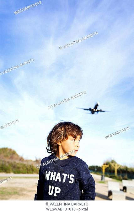 Little boy looking over shoulder to airplane in background
