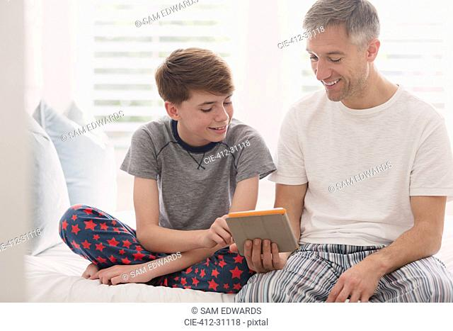 Father and son in pajamas using digital tablet