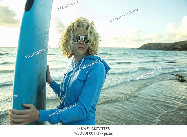Portrait of teenage girl standing on the beach with her surfboard