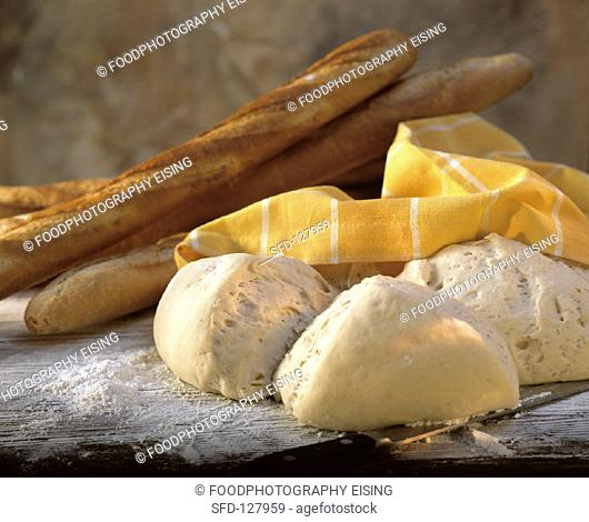 Baking still life: yeast dough & baguettes on wooden table