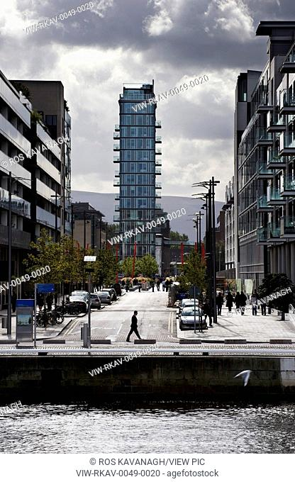 Altro Vetro, Dublin, Ireland. Architect: Shay Cleary Architects, 2008. View of tower from North Wall Quay showing river, adjacent buildings pedestrians