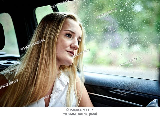 Serious blond young woman in a car at a rainy day