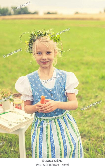 Germany, Saxony, portrait of smiling girl with floral wreath and dirndl holding carrot in her hand