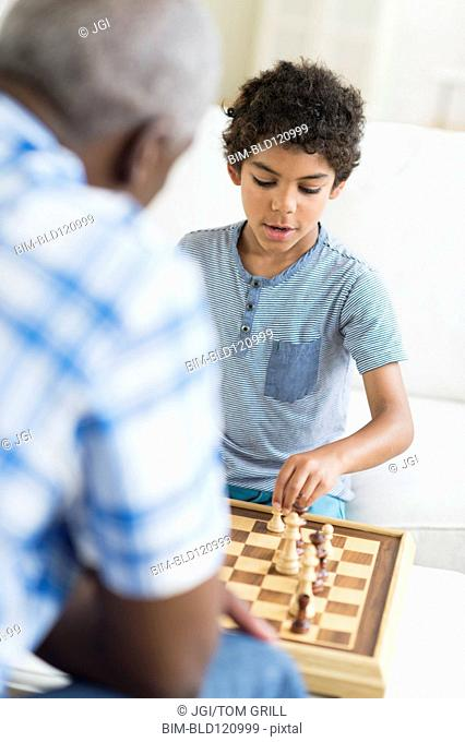 Boy playing chess with grandfather
