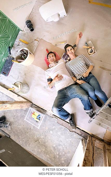 Happy couple renovating new home, taking a break, daydreaming
