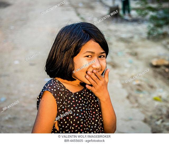 Little native girl smiling mischievously, portrait, Yangon, Myanmar