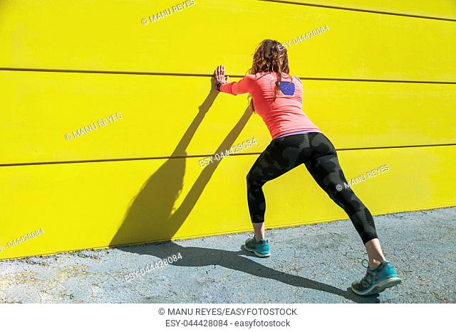 young woman stretching on a yellow wall before running