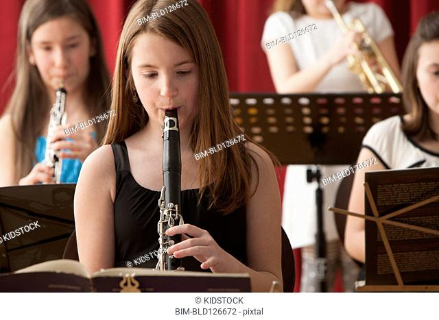 Caucasian girl playing clarinet in performance