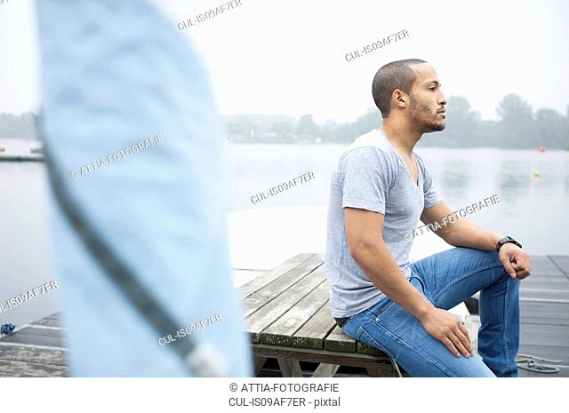 Young man sitting on jetty