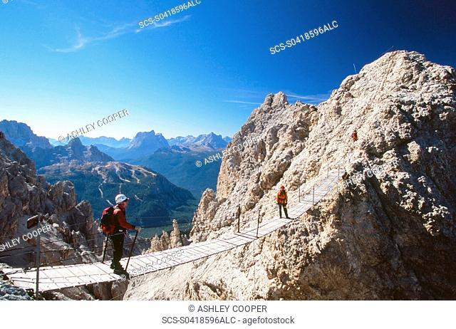 A mountaineer on a via ferrata bridge in the Italian Dolomites