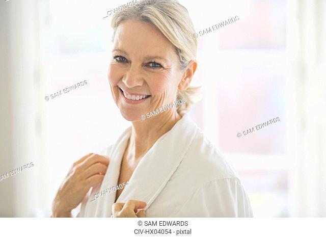 Portrait smiling, confident mature woman in bathrobe