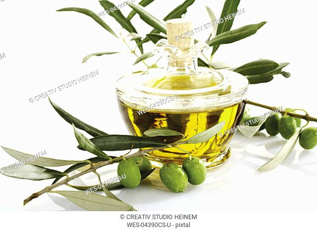 Fresh olives on twig and carafe of olive oil