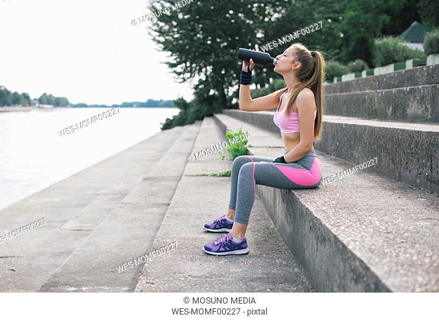 Sporty woman drinking water at the riverbank