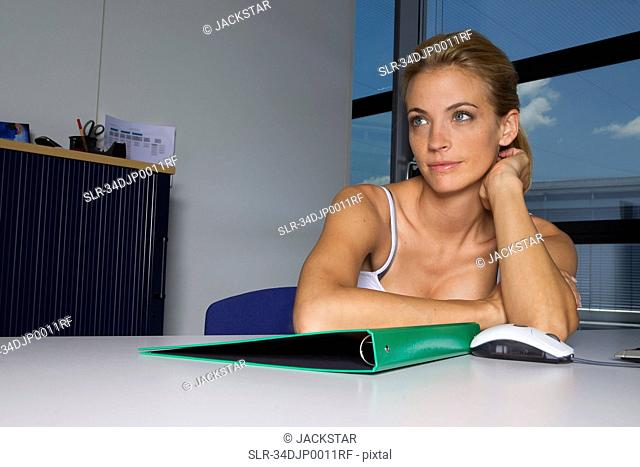 Woman sitting with folder at desk