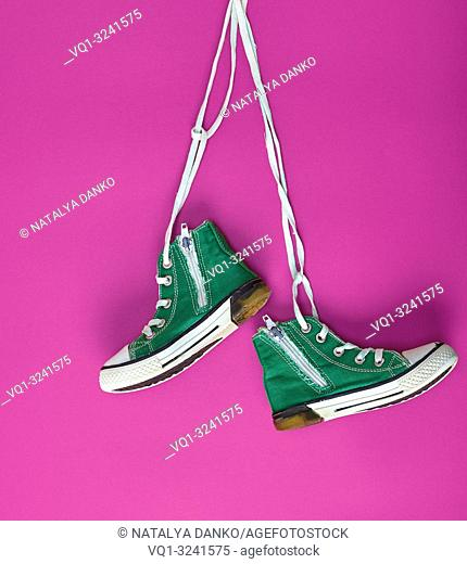 pair of green textile sneakers hanging on bella lace, pink background
