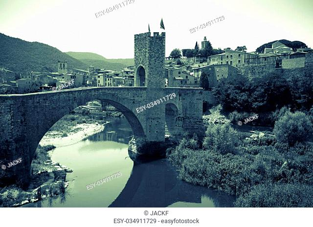Retro photo of medieval town with gate on bridge. Besalu, Catalonia
