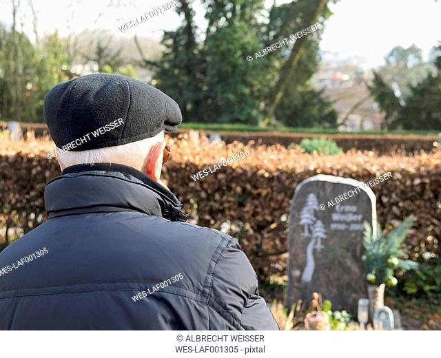 Old man on graveyard looking at gravestone