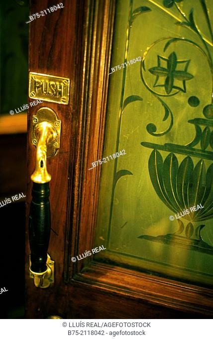 Ancient carved glass door of a pub with a shooter in the foreground and a sign with the word Push. London, England, UK, Europe