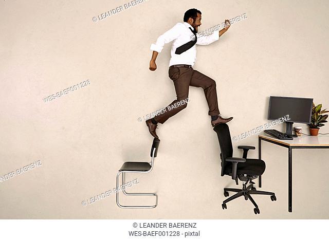 Businessman walking on chairs towards office desk