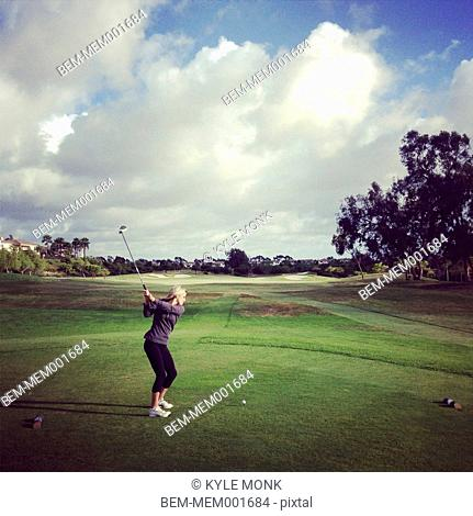Caucasian woman playing golf on course