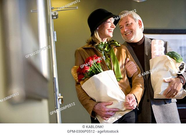 Portrait of mature couple holding groceries in modern downtown loft