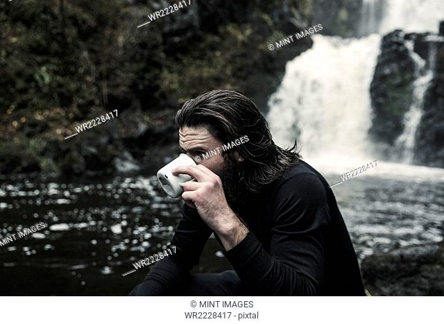 Wild camping. A man drinking from a cup by a fast flowing stream