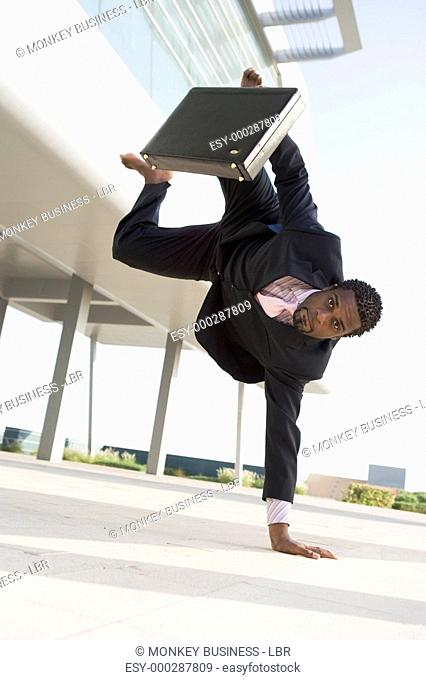 Businessman outdoors by building standing on one hand