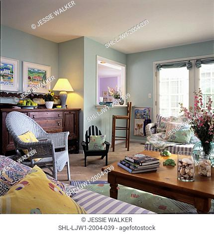 LIVING ROOMS - View to kitchen pass through. Mint green walls, wicker chairs and sofa, pastel mixed pattern pillows, pine coffee table