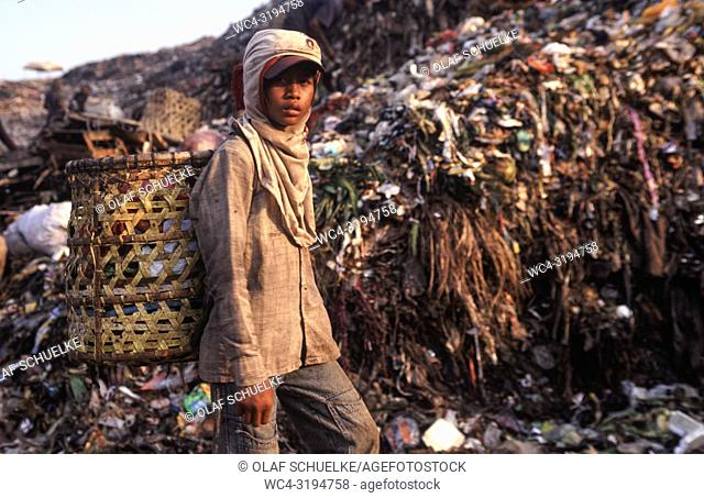Jakarta, Java, Indonesia, Asia - An Indonesian garbage collector is searching for recyclable materials like plastic and metal at the Bantar Gebang garbage dump...