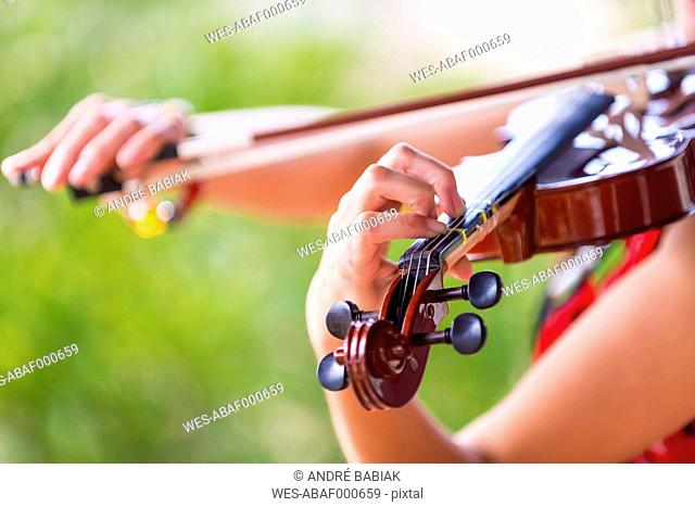 USA, Texas, Young woman playing violin, close up