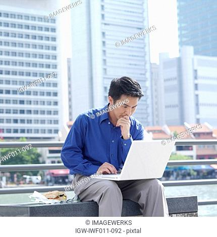 Businessman sitting on a bench using a laptop