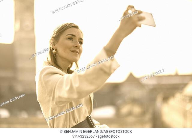 stylish blogger woman taking selfie with smartphone next to church Marienkirche, Frauenkirche, self perception, in Munich, Bavaria, Germany
