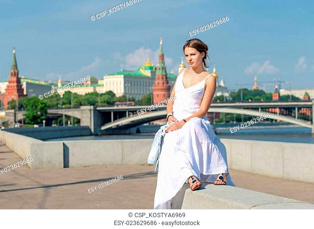 Beautiful girl in white dress sitting on the parapet of the emba