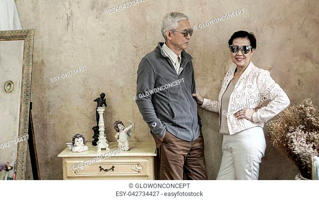 Happy Asian senior couple casual dress with sunglasses in vintage style house