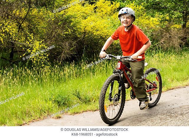 10 year old boy bicycling on Saturna Island, Gulf Islands, BC, Canada