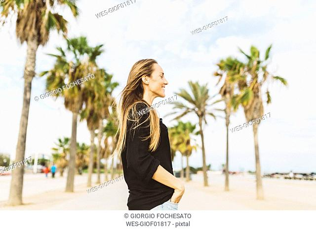 Smiling young woman on waterfront promenade