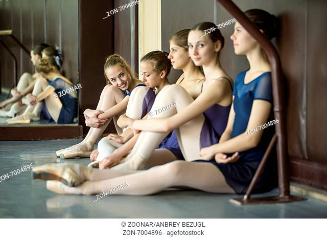 Five young dancers in the same dance costumes, resting sitting o