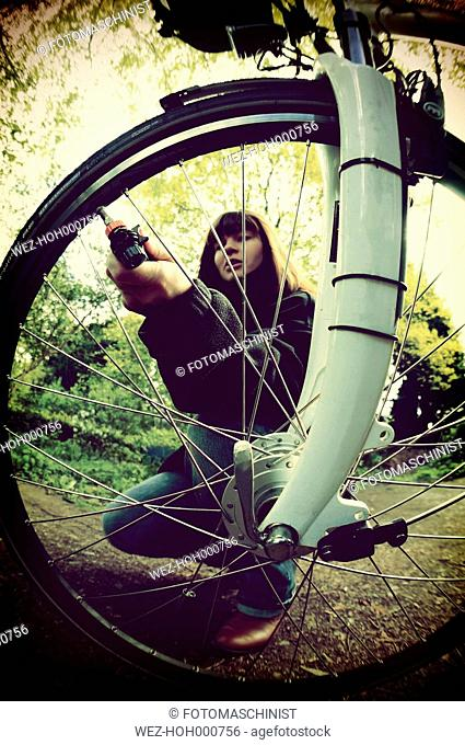 Woman inflating bicycle tire