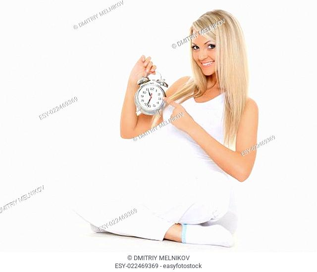 Young sporty woman with alarm clock